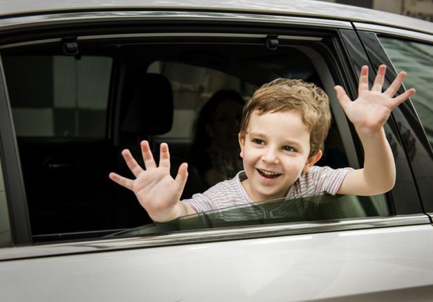 dreng i bil på vej til ferie